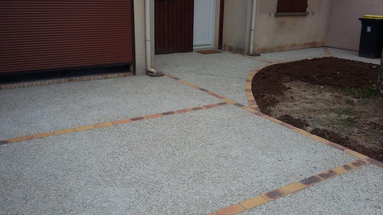 Allée en béton désactivé gravillon roulé et décor en brique jaune flambé
